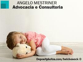 Criança loira triste, deitada no chão e abraçada com um ursinho.
